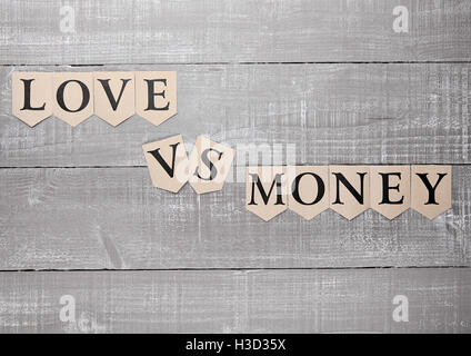 love vs money paper letters symbol motivation sign on wooden board - Stock Photo