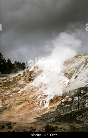 Smoke emitting from volcanic landscape against cloudy sky - Stock Photo