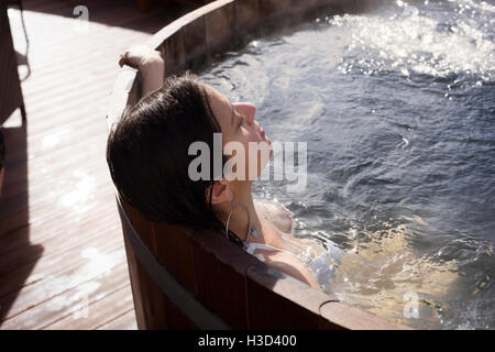 Woman relaxing in wooden bathtub on sunny day - Stock Photo