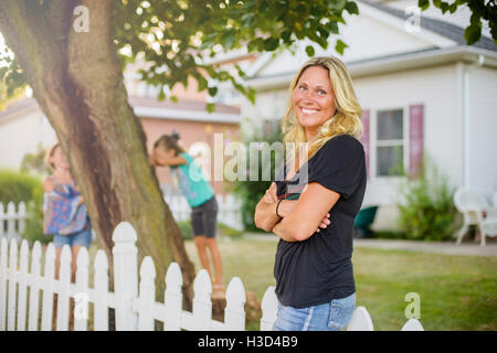 Happy woman looking away while children playing hide and seek in backyard - Stock Photo