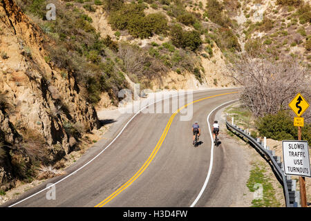 High angle view of friends cycling on mountain road - Stock Photo