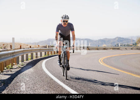 Man cycling on road against clear sky - Stock Photo