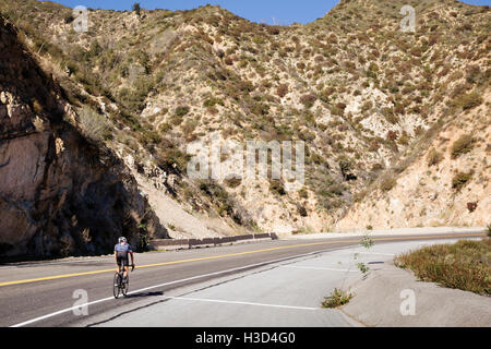 Man cycling on road by majestic mountain - Stock Photo