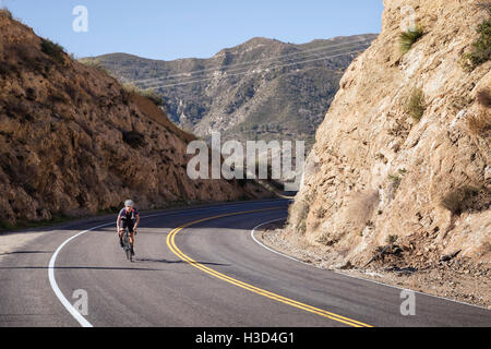 Man biking on road amidst mountains - Stock Photo