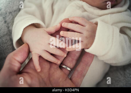 Close-up of baby holding father's hand while lying on bed - Stock Photo