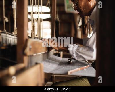 A man weaving silk in Inle Lake, Myanmar (Burma) - Stock Photo