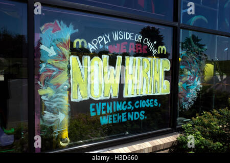 Large colorful graphic now hiring sign on McDonald's  Restaurant window.  St Paul Minnesota MN USA - Stock Photo