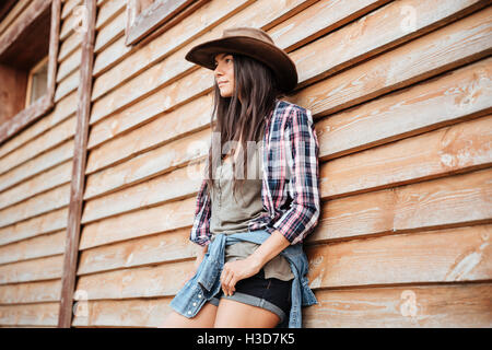 Portrait of attractive young womna cowgirl in hat standing near the house - Stock Photo