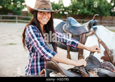 Smiling pretty young woman cowgirl standing and preparing saddle for riding horse - Stock Photo