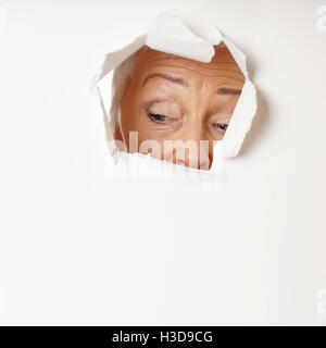 curious mature woman looking through hole - Stock Photo