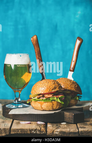 Beef burgers with crispy bacon, vegetables and glass of beer - Stock Photo