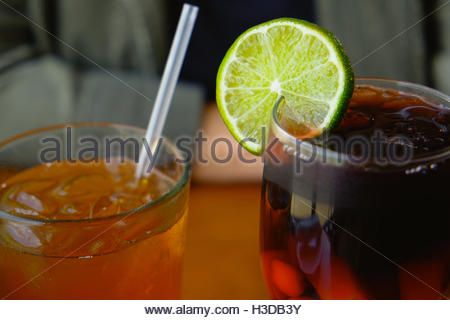 A slice of lime in a glass of sangria and a straw in a glass of ice tea at a restaurant. - Stock Photo
