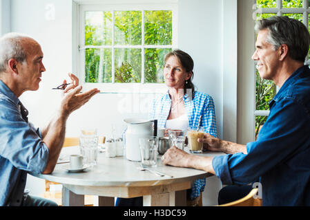 Two men and a woman seated at a coffee shop table talking. - Stock Photo