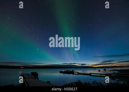 Star Trails and Aurora - Long exposure to capture star trails and light aurora borealis over a lake after sunset. - Stock Photo