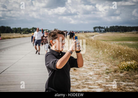 Little kid boy taking picture to the Mont Saint Michel, Britany, France - Stock Photo