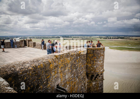 People visiting Mont Saint Michel monastery, Brittany, France enjoying the view from the famous island commune - Stock Photo