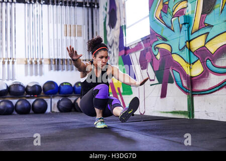 A female athlete trains in a crossfit gym. - Stock Photo