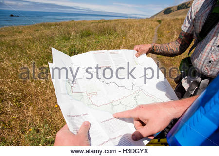Two backpackers reading a map - Stock Photo