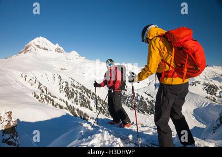 Two skiers on the summit of the Gargoyles near Elfin Lakes in Garibaldi Provincial Park, British Columbia, Canada. - Stock Photo