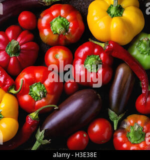 Variety of colorful red, green, yellow paprika bell peppers, chili peppers, tomatoes and eggplants over old texture - Stock Photo