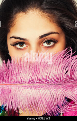 Beautiful young woman hiding face with pink feather - Stock Photo