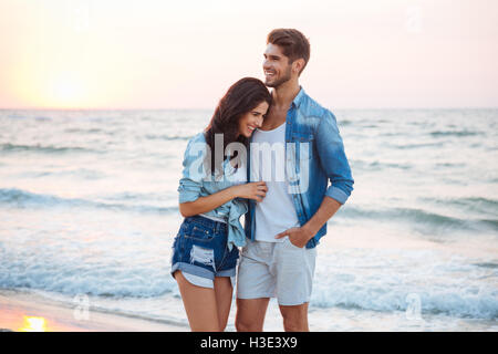 Happy young couple hugging and laughing on the beach - Stock Photo