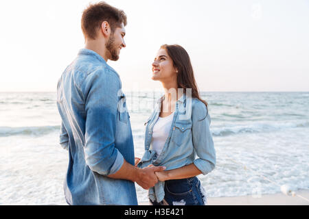 Happy young couple in love standing and holding hands on the beach - Stock Photo