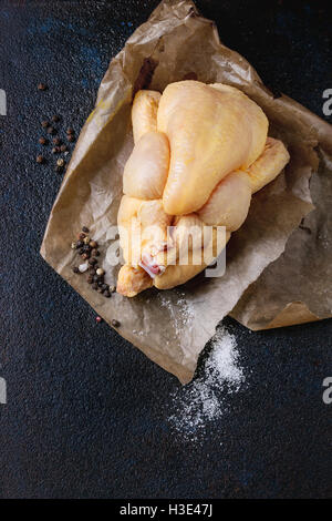 Whole raw mini chicken on baking paper with seasoning sea salt and pepper over black textural background. Overhead - Stock Photo