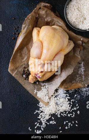 Whole raw mini chicken on baking paper with seasoning and bowl of uncooked white rice over black textural background. - Stock Photo