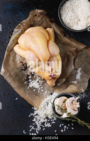 Whole raw mini chicken on baking paper with seasoning, thyme, sliced mushrooms and bowl of uncooked white rice over - Stock Photo
