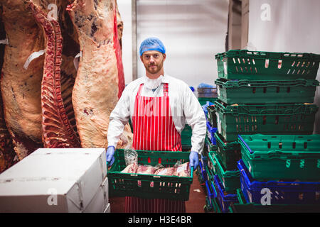 Portrait of butcher carrying a crate of red meat in storage room - Stock Photo