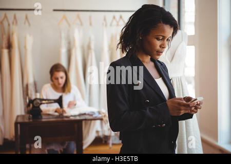 Fashion designer using mobile phone - Stock Photo