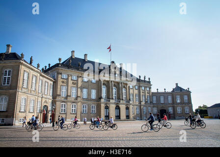 Cyclists pass in front of one of the buildings of the Amalienborg Palace the official residence of the Danish Royal's, - Stock Photo