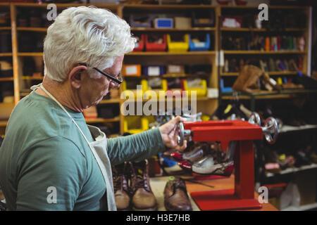 Shoemaker working with stretcher machine - Stock Photo