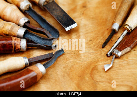 Vintage tools of woodcarving closeup on wooden background - Stock Photo