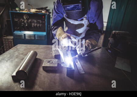 Female welder working on a piece of metal - Stock Photo