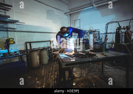 Male welder working on a piece of metal - Stock Photo
