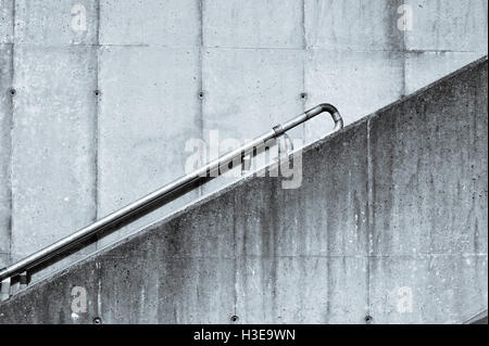 Concrete Access Stairway with an Inclined Steel Handrail in Toned Monochrome - Stock Photo