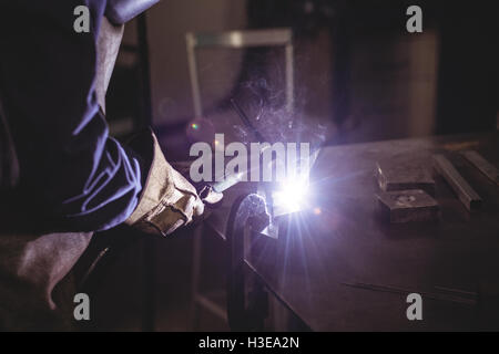 Mid-section of female welder working on a piece of metal - Stock Photo