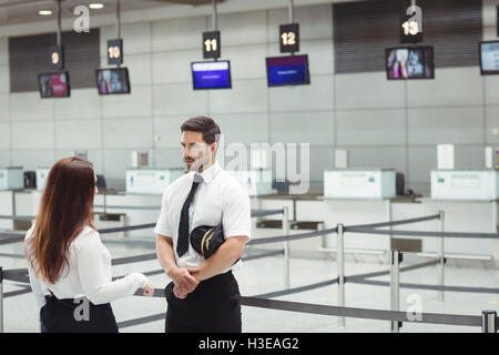 Pilot and flight attendant interacting with each other - Stock Photo