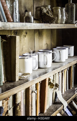 Warm toned image of white enamel mugs, glass jars and books on shelves in an old bookcase or dresser - Stock Photo