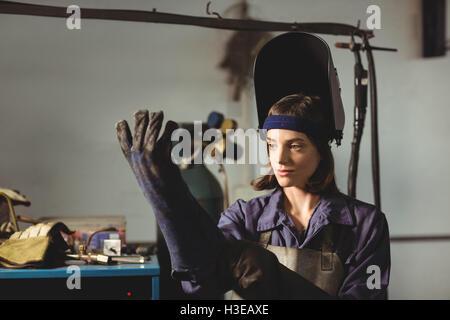 Female welder wearing glove - Stock Photo