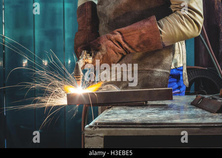 Mid-section of male welder working on a piece of metal - Stock Photo
