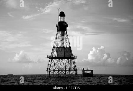 On a serene calm morning,Florida's Fowey Rocks Lighthouse greets the early light of day in this black and white - Stock Photo