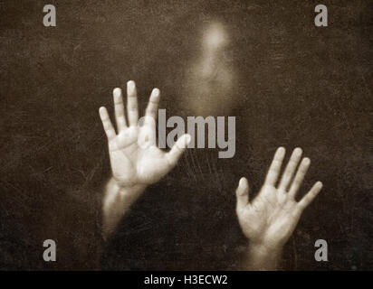 Shadowy figure behind dusty scratched glass - Stock Photo