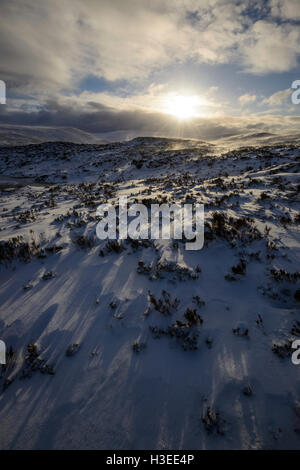 Sun breaking through clouds on a snow covered moorland, Grey Mare's Tail Nature Reserve, near Moffat, Dumfries & - Stock Photo