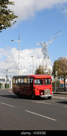 City Sightseeing bus on Oxford Street, Belfast, Northern Ireland with the Thanksgiving Statue in the background. - Stock Photo