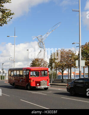 Red single decker City Sightseeing bus in Belfast, at Oxford Street, Belfast, Northern Ireland with the Thanksgiving - Stock Photo