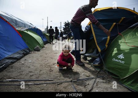 A Syrian boy stands outside his tent, as his father fixes it, at a refugee camp in the northern Greek village of - Stock Photo