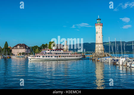 Ferry or tour boat entering the harbor at Lindau on Lake Constance passing the historic lighthouse with its clock - Stock Photo